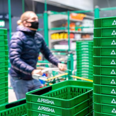 Henkilö ostoskärryn kanssa ostoskorien vieressä Prismassa.
