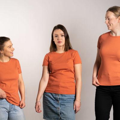 Kolmella eri mittaisella naisella sama oranssi t-paita päällä.