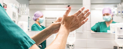 En sjukskötare tvättar händerna i ett badrum. I spegeln syns två sjukskötare som bär ansiktsskydd.
