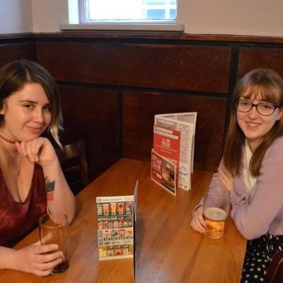 Två unga kvinnor sitter mittemot varandra vid ett bord i en pub.