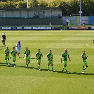 En fotbollsplan som det går människor på. I förgrunden går 10 män i en rad, de är klädda i gröna shorts och tröjor med svarta och gröna tröjor.