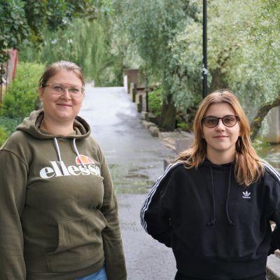 Två unga kvinnor står på en gångväg.