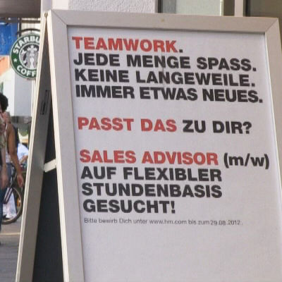 En skylt på en tysk gata som gör reklam för jobb.