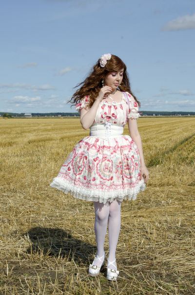7e13a3cf0b2b En kvinna klädd i så kallade Lolitakläder - en fluffig vit och rosa klänning  med spetsar