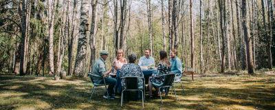 Kuvan etualalla kuusi henkilöä istuu pöydän ääressä ulkosalla kahvilla. Taustalla keväinen koivikko ilman lehtiä.