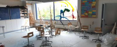 Ett klassrum med stolar huller om buller och sprayad färg på fönstret.