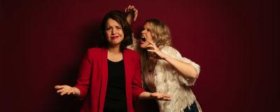 Två kvinnor poserar framför fondvägg,