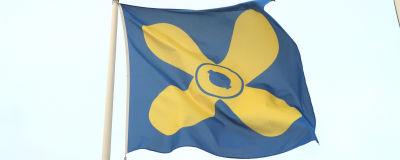 Kimitoöns blåa flagga med en gul propeller i mitten mot en ljusblå himmel.