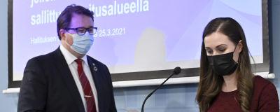 Sanna Marin och Mika Salminen på en presskonferens. Båda bär munskydd.