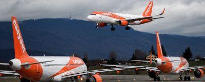 Två orange Easyjet-flygplan på landningsbanan och ett i luften.