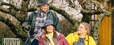 Kädet multaan -ohjelman juontajat Inkeri Alatalo, Taina Suonio ja Enni Koistinen istuvat puun edessä.