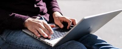 En person använder en laptop utomhus.
