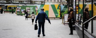 Kuvassa vanhus kävelee Helsingin keskustassa.