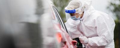 En person utför ett coronatest på en patient som sitter i sin bil (endast bilen syns på bilden). Persoenn som utför testet har skyddsdräkt på sig.