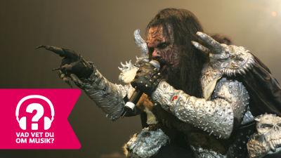 Mr. Lordi sjunger i en mikrofon och pekar mot publiken.