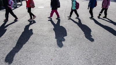Skolelever går i kö med säkerhetsavstånd mellan varandra. De kastar långa skuggor mot asfalten.