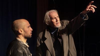 En äldre man med vitt skägg står och pratar en yngre man.