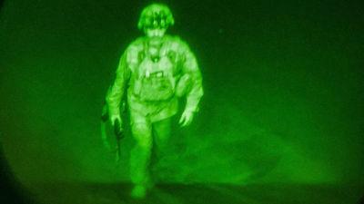 Den sista amerikanska soldaten i Afghanistan generalmajor Chris Dunahue stiger in i ett transportplan. Det är natt och bilden är tagen genom en mörkerlins.