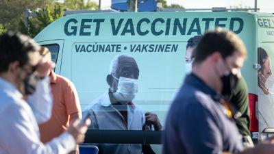 """Ihmiset jonottavat koronarokotukseen Floridassa taustalla rokotuskampanjatarralla peitetty bussi, jossa lukee """"ota rokote!""""."""