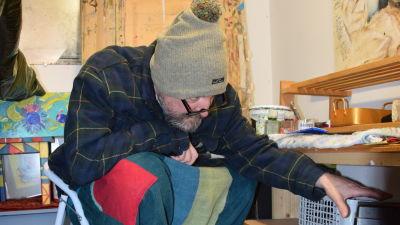 en konstnär iklädd mössa fryser och arbetar i sitt kalla garage