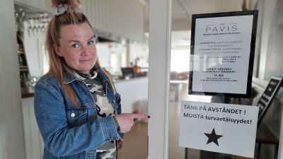 Emma Sandström-Sunqvist, krögare på Pavis pekar på en skylt om säkerhetsavstånd under coronatider.