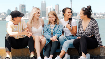 Au pairit Uudessa-Seelannissa -sarjan au pairit istuvat meren äärellä kaupungin siluetti taustalla.