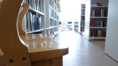 En gammal trästol i en ny ljus biblioteksmiljö. Vita hyllor fyllda med böcker. Ljus strömmar in genom ett fönster.
