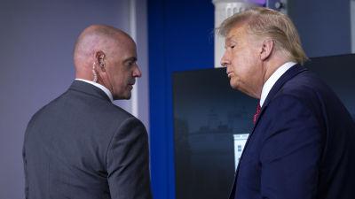 En Secret Service-agent talar med president Donald Trump.
