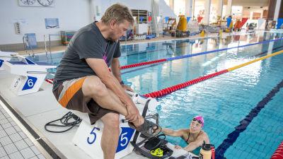 Valmentaja Marko Malvela ja uimari Fanny Teijonsalo juttelevat altaan reunalla harjoituksissa.