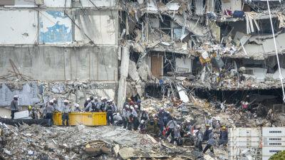 räddningsarbetare jobbar vid foten till ett höghus som kollapsat