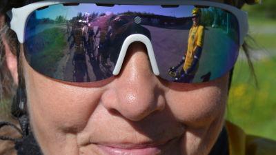 Mariella Ramstedt, en dam med solglasögon och gul cykelhjälm. Hennes medcyklister speglas i solglasögonen.