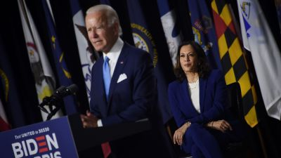 Joe Biden står i en talarstol och Kamala Harris sitter på en stol snett bakom honom och tittar på.