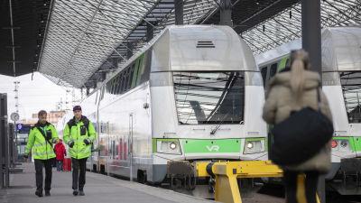ett tåg som stannat på perrongen på järnvägsstationen. Framför tåget går två lokförare och två resenärer.