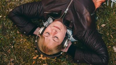 Nainen kuuntelee kuulokkeista musiikkia nurmikolla.