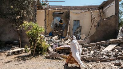 En kvinna framför ett skadat hus i Wukro norr om Mekele i Etiopien