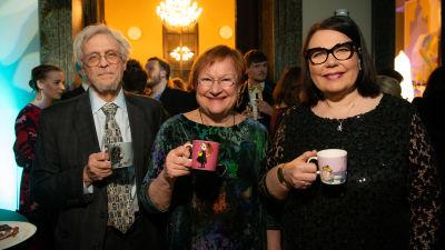 Presidentti Tarja Halonen, Pentti Arajärvi ja Ylen toimitusjohtaja Merja Ylä-Anttila hymeilevät kameralle muumimukit käsissään.