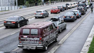 """Bilkö utanför riksdagshuset. På en av bilarna står det """"Stop! autoilijoiden kuritukselle!"""", ungefär """"sluta straffa bilisterna"""" på svenska."""