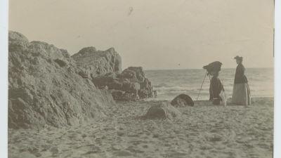 Kvinna fotograferar på stranden på Île Saint-Honorat i Cannes, sekelskiftet 1800-1900.