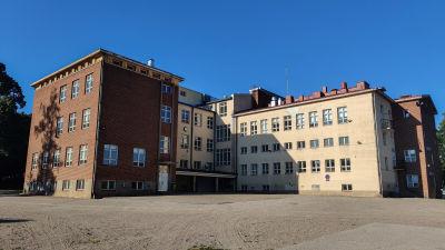 En tom skolgård och skolbyggnad.