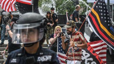 En polis i skyddsutrustning står i förgrunden, i bakgrunden demonstranter som håller i amerikanska flaggan.