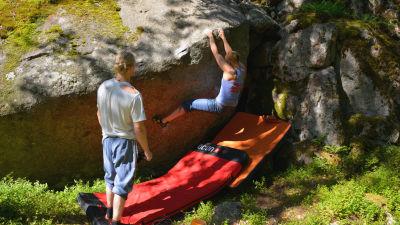 Carolina Mikander hänger på baksidan av stenen och värmer upp.