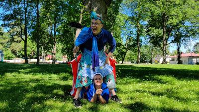 En man och en kvinna utklädda till städerskor i en lummig park.
