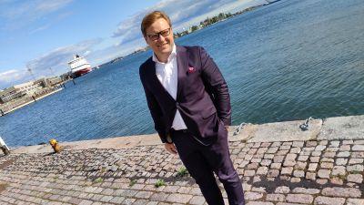 En ung man med ljust hår står i kostym framför havet. I bakgrunden syns två fartyg. Han ser in i kameran och ler.