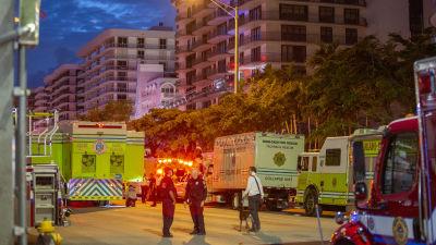 Gula räddningsfordon står på en mörk gata med rödlysen på. I bakgrunden syns höghus och en blå natthimmel.