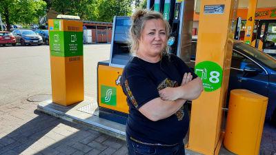 En kvinna står med händerna i kors framför en tankningspunkt på en bensinstation,