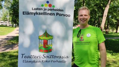 En man iklädd neongrön t-skjorta står bredvid ett högt plakat.