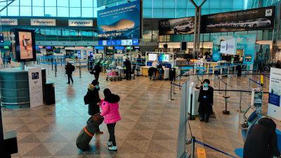 Några personer inne vid en incheckningspunkt på ett flygfält.