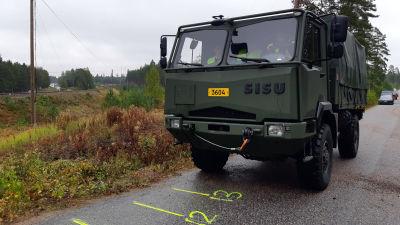 Ett grönt militärfordon på en asfalterad väg i närheten av ett järnvägsspår.