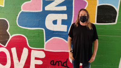 Bildkonstterapeut Michael Rahikainen står framför en färggrann vägg i Kabelfabriken i Helsingfors.