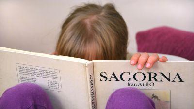 Barn läser bok med klassiska sagor.
